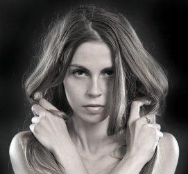 Mulher com cabelos soltos segurando os fios